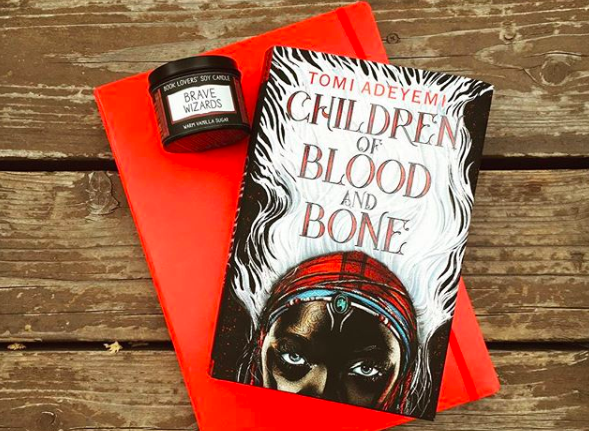 "Novel CHILDREN OF BLOOD AND BONE on top of red journal next to ""brave wizards"" candle"