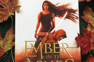 An Ember in the Ashes by Sabaa Tahir surround by red maple leaves
