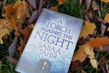 Novel A TORCH AGAINST THE NIGHT with grass and fallen leaves