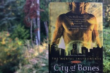 Hand holding hardcover edition of City of Bones against a backdrop of Pacific Northwest forest