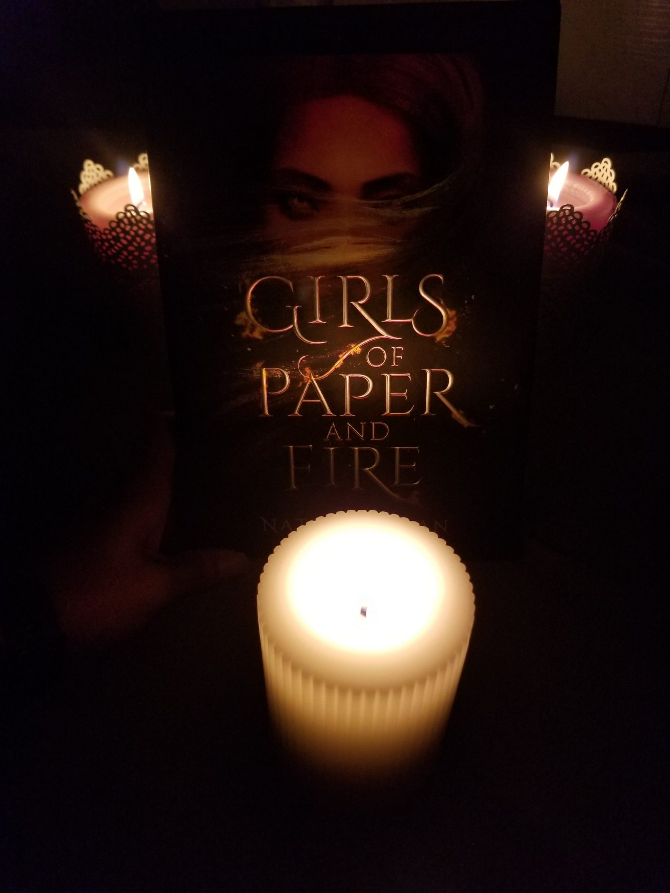 Novel GIRLS OF PAPER AND FIRE surrounded by three candles
