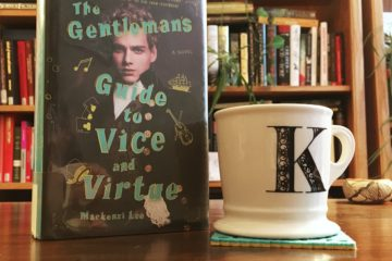 "Hardcover copy of Mackenzi Lee's A Gentleman's Guide to Vice and Virtue sits on a dark wood desk next to a white mug with a ""k"" on it. Bookshelves in the backgroud"