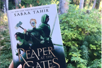 White hand holds A REAPER AT THE GATES with lush forest in the background