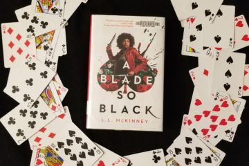 Novel A BLADE SO BLACK surrounded by a circle of playing cards