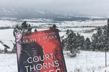 A Court of Thorns and Roses by Sarah J. Maas in front of the snowy CO front range