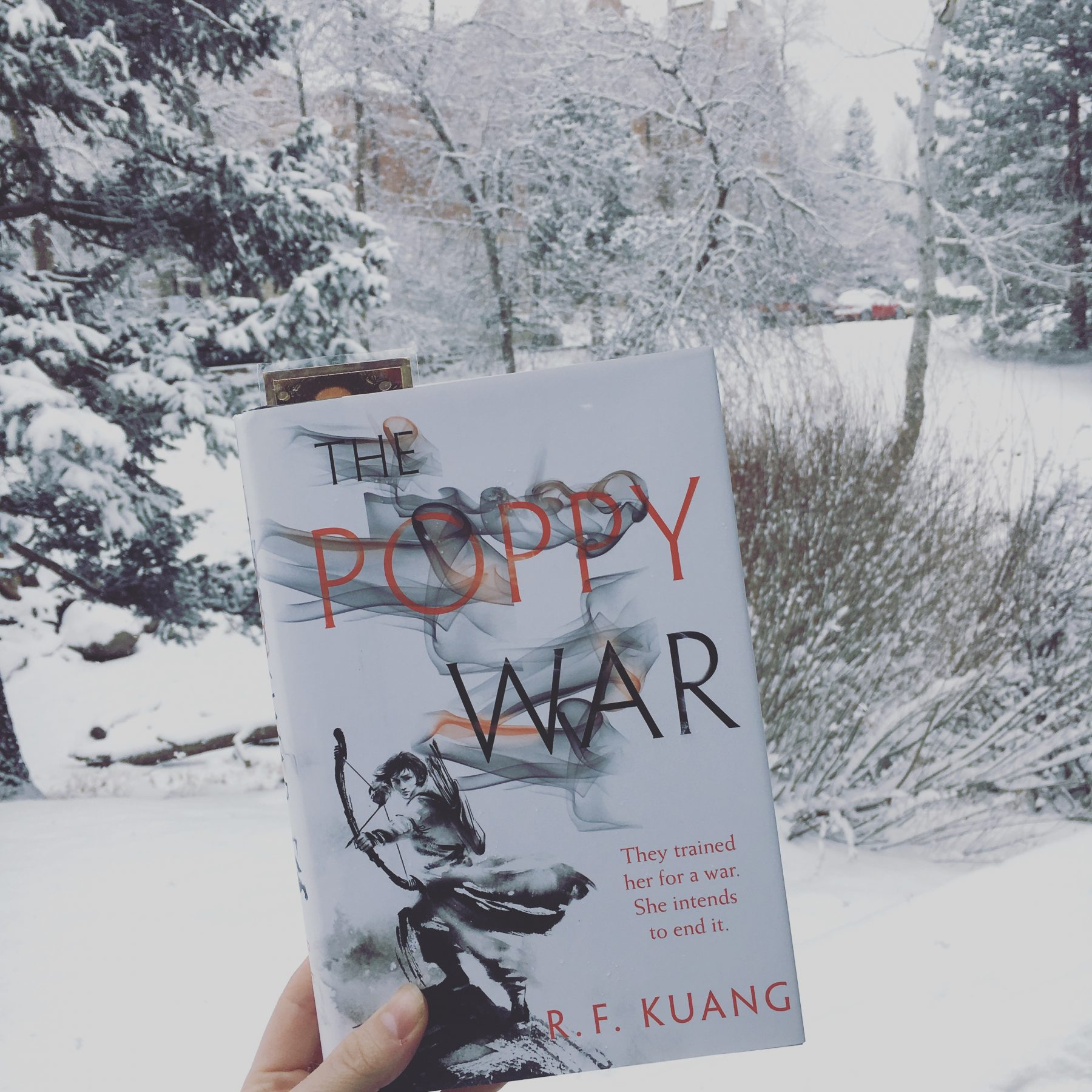 The Poppy War by RF Kuang against the backdrop of a snowy landscape