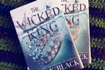 Two hardcover copies of the The WIcked King on top of a navy and green crocheted blanket