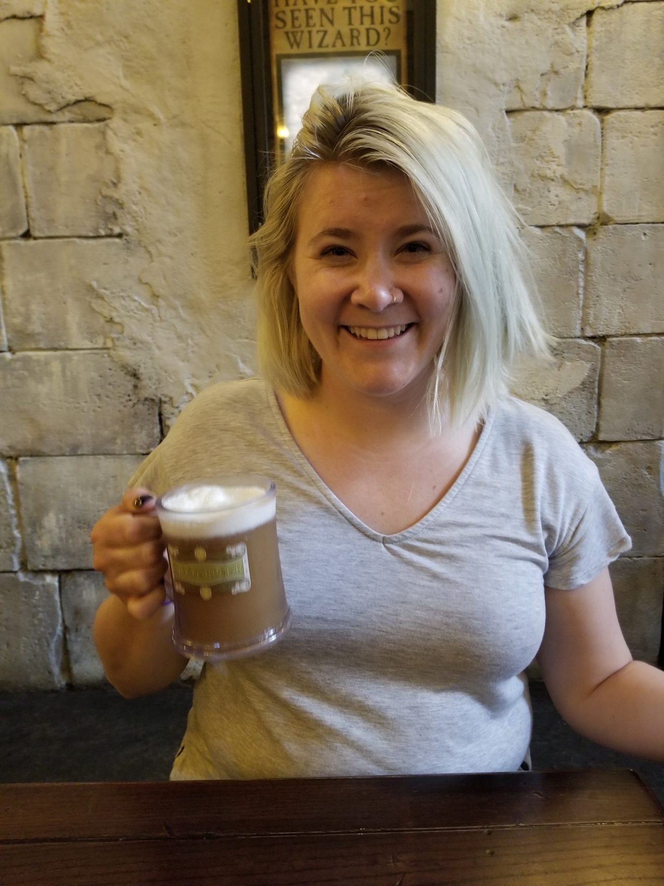 Kelly smiles with a mug of butter beer in her hand