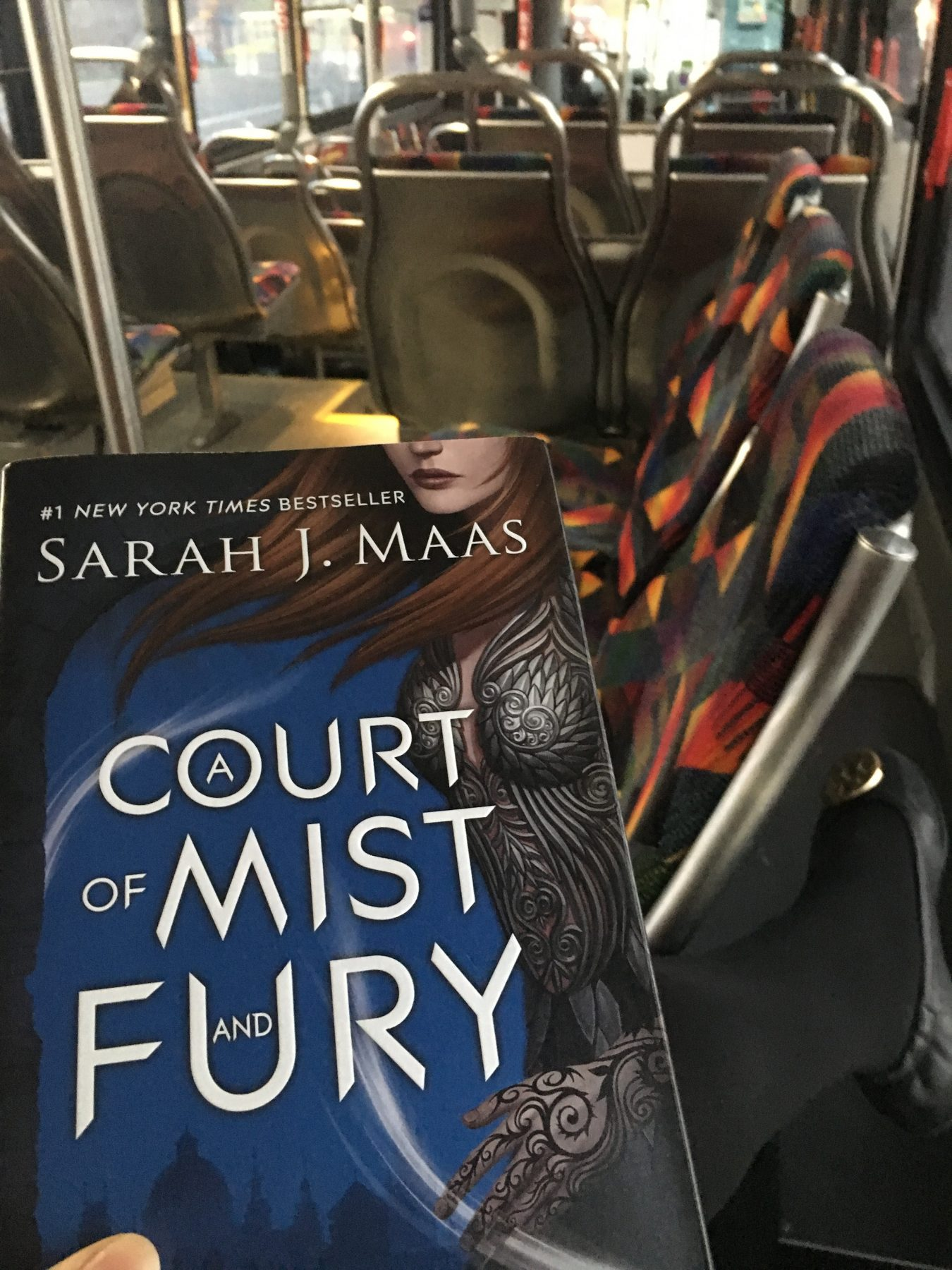 Hardcover copy of A Court of Mist and Fury with bus seats in the background