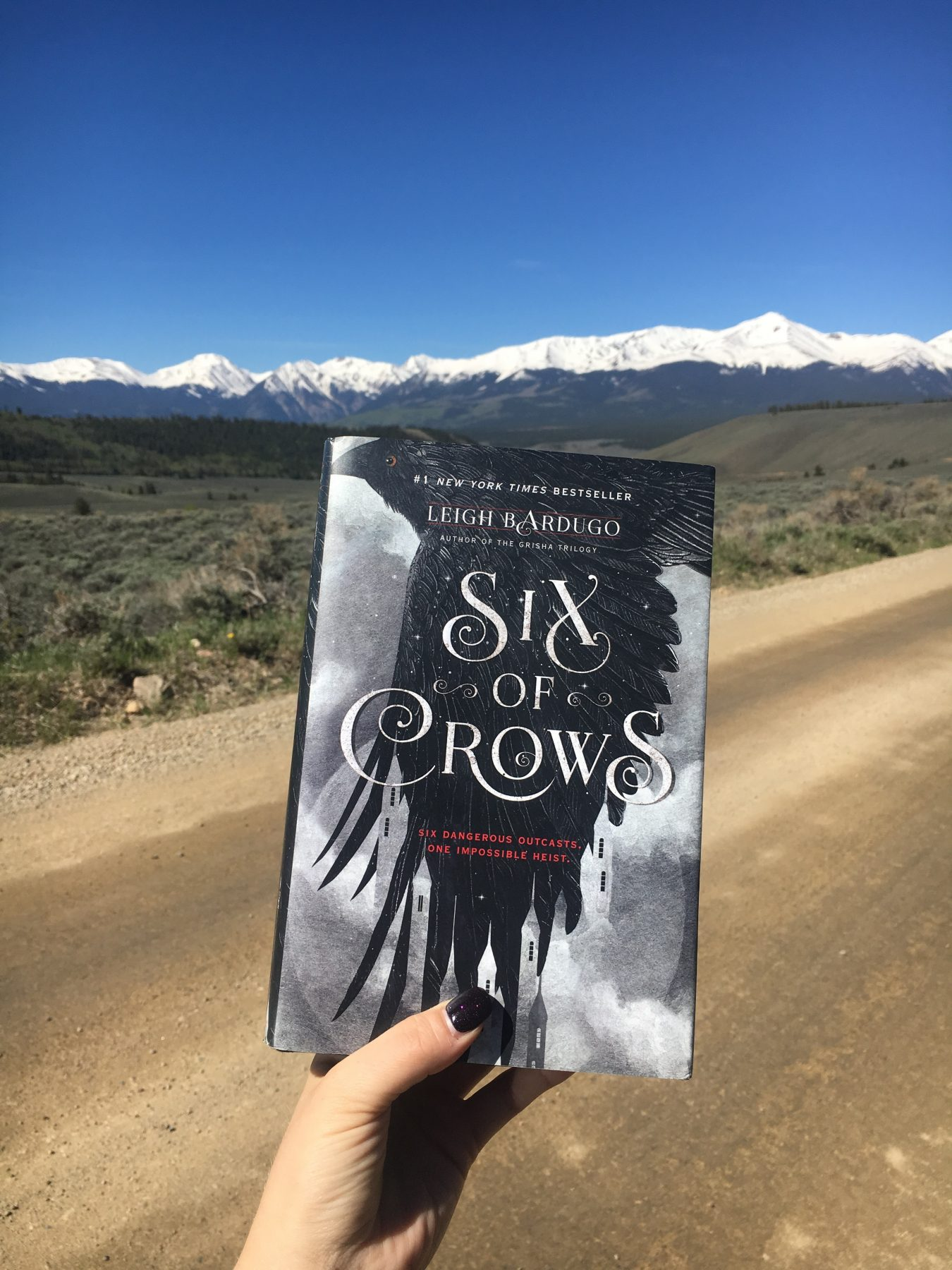 Hardcover copy of Six of Crows in front of a winding dirt road. Background is snowy mountains and bright blue sky