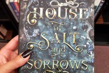 Light-skinned black hand holds HOUSE OF SALT AND SORROWS