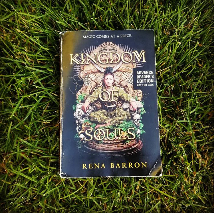 Paperback version of Rena Barron's KINGDOM OF SOULS lies on bright green grass