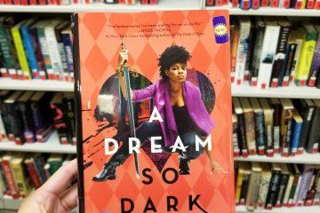 Light-skinned brown hand holds novel A DREAM SO DARK. Shelves of library books in the background.