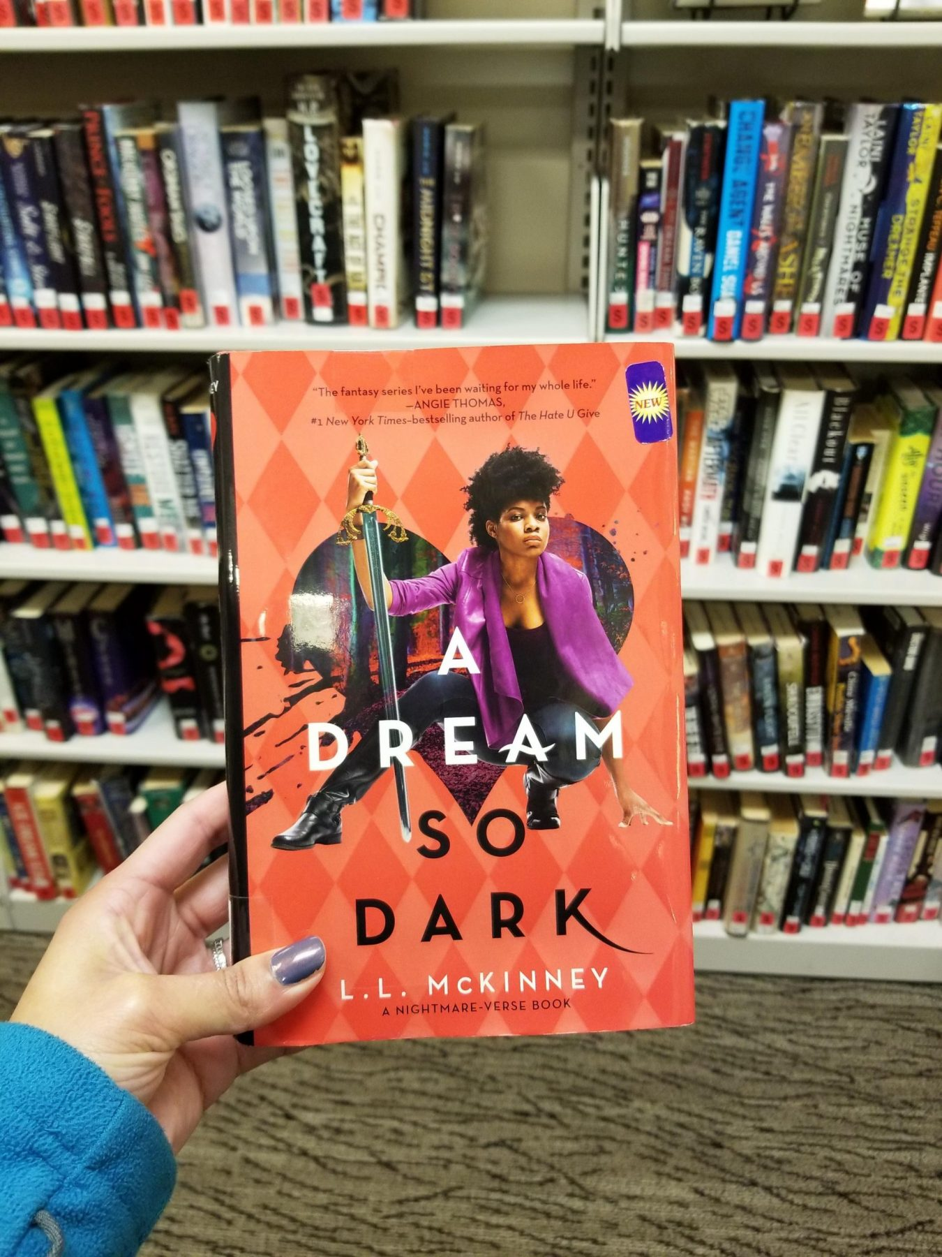 Light-skinned brown hand holds novel A DREAM SO DARK. Shelves of library books in the background.