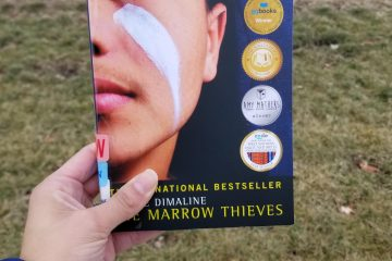 Paperback copy of The Marrow Thieves held in J's left hand. A natural landscape of greens and browns is in the background.