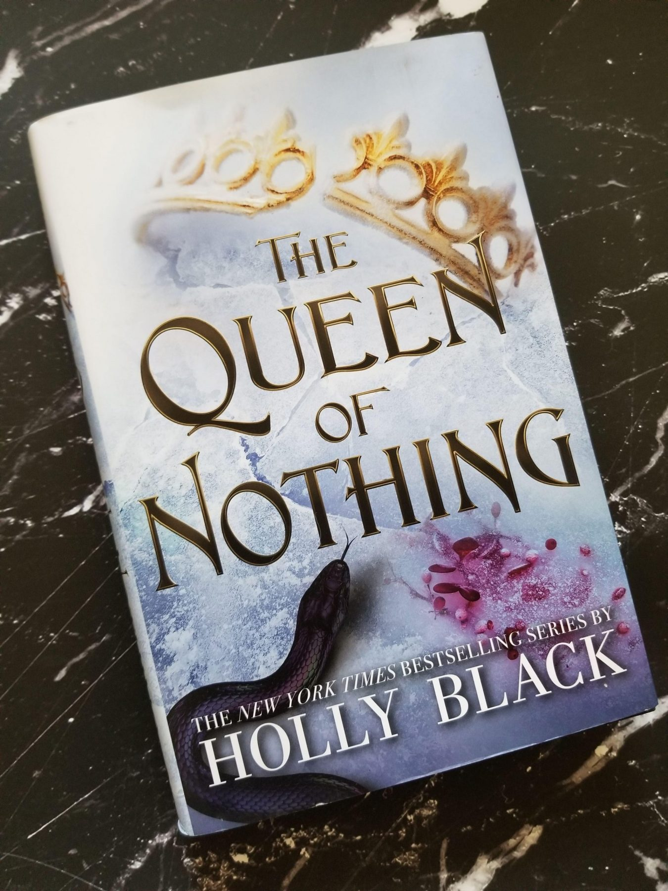 hardcover of the Queen of Nothing on a black marble background