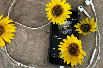 Crier's War audiobook pulled up on an iphone screen with sunflowers draped across the phone, and headphones surrounding the phone and flowers