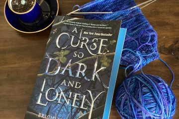 A paperback copy of A CURSE SO DARK AND LONELY by Brigid Kemmerer sits on top of a brown wood desk. A small succulent in a tiny navy teacup/saucer with gold trim sits to the left. To the right, a half-finished sock on double-pointed knitting needles rests by a ball of yarn (variegated blues and purples)