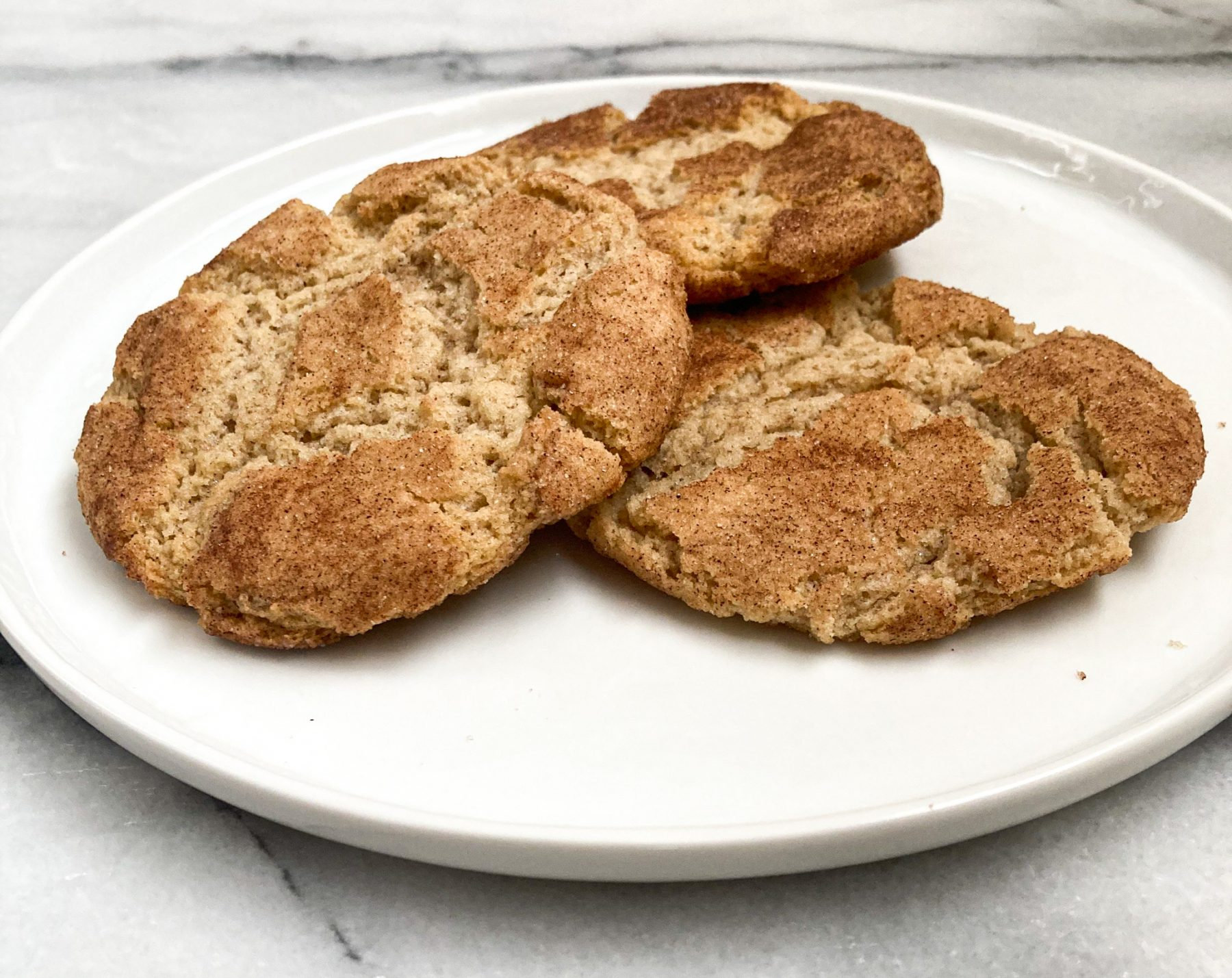 Three snickerdoodle cookies stacked on a white plate