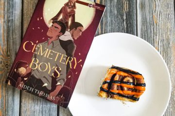 Novel CEMETARY BOYS by Aidan Thomas rests on a wood plank background. A white plate sits beside the book with a cinnamon roll that has black and orange striped icing