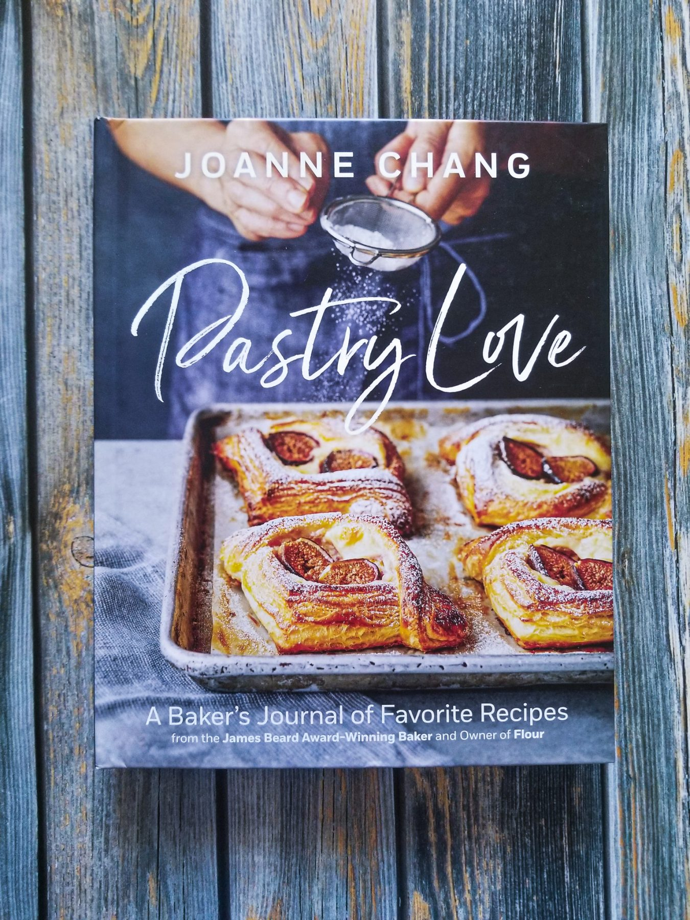 hardcover of Joanne Chang's PASTRY LOVE lays on top of a wood plank background