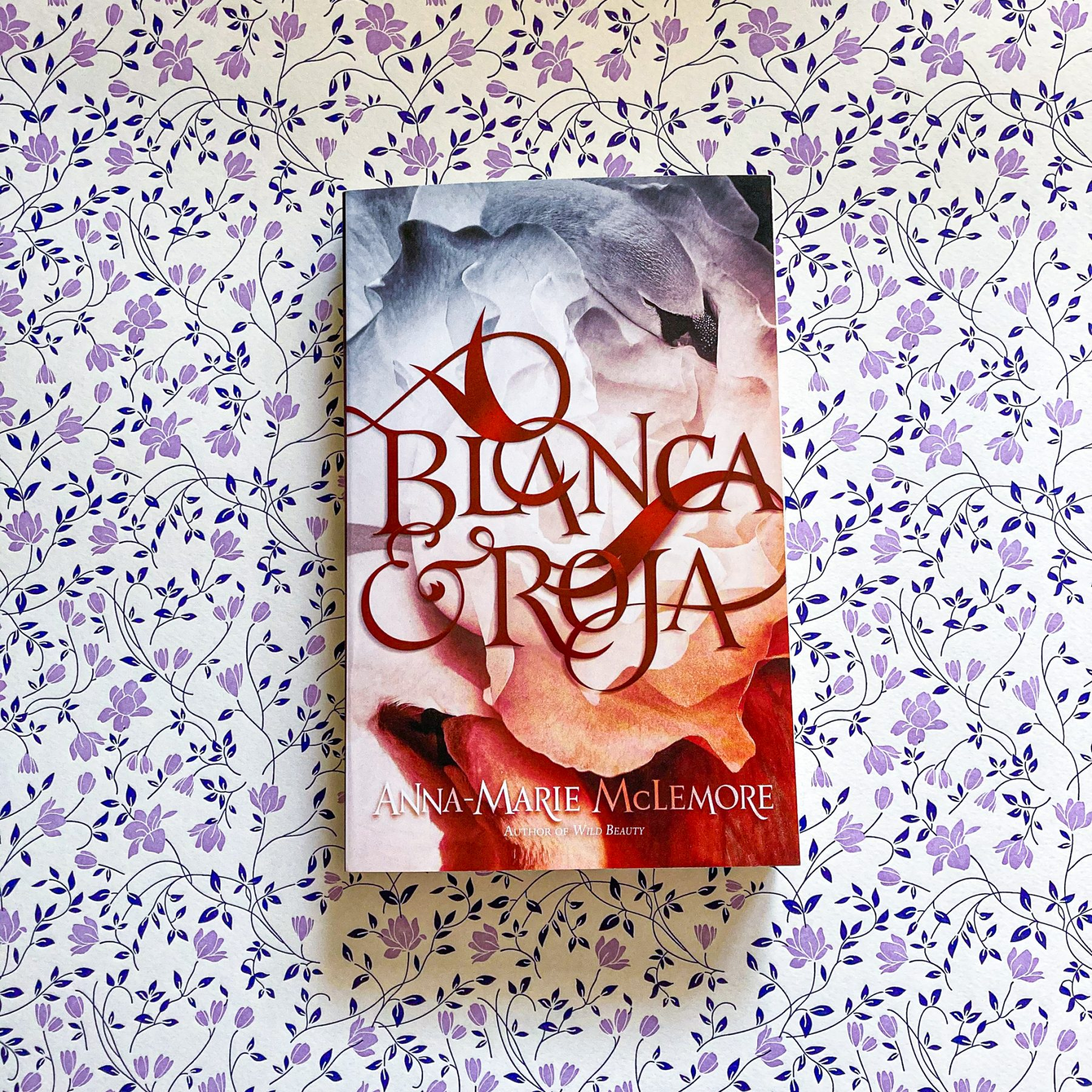 Paperback copy of Blanca & Roja rests on background of purple and navy flowers
