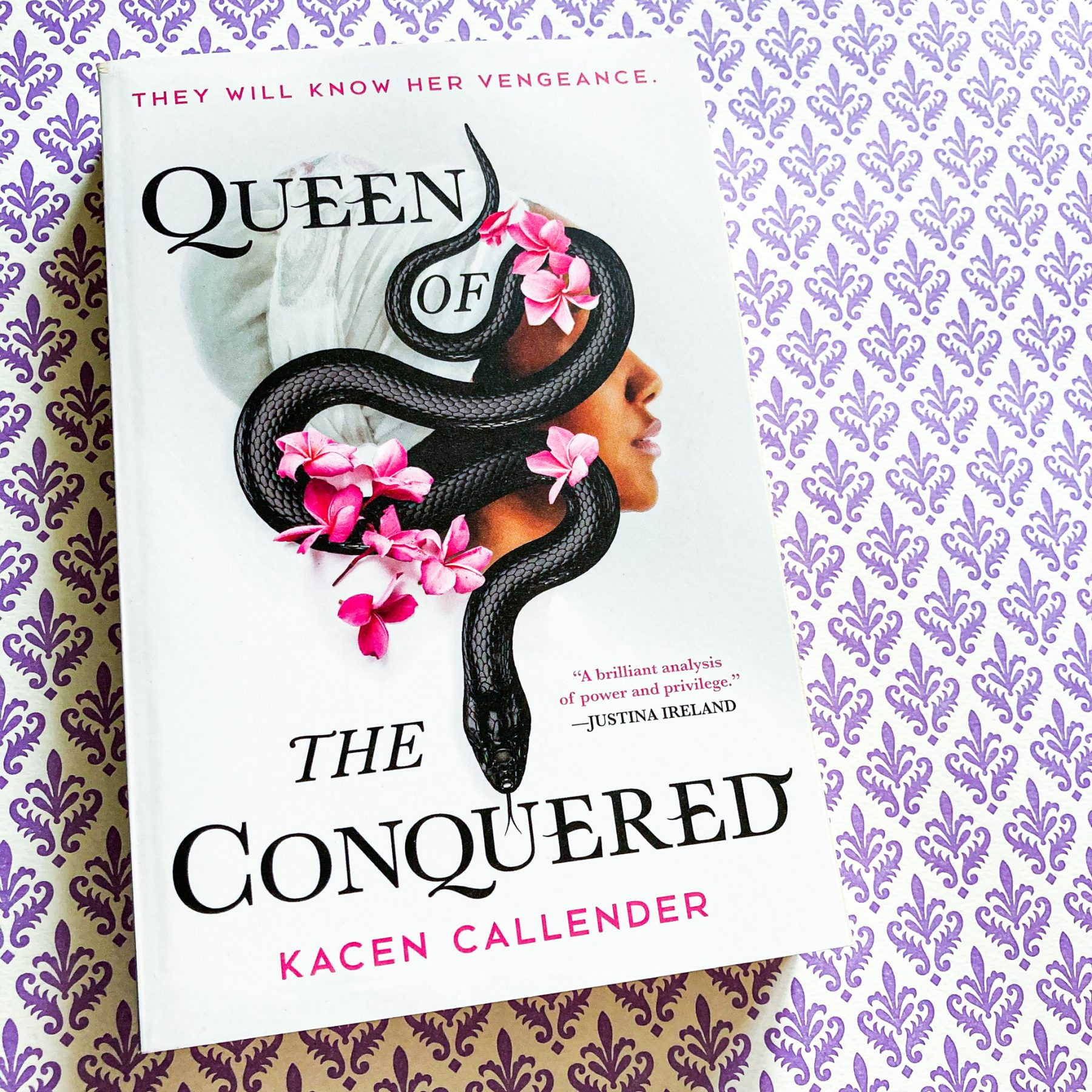 paperback copy of Queen of the Conquered on top of a purple and white decorative paper