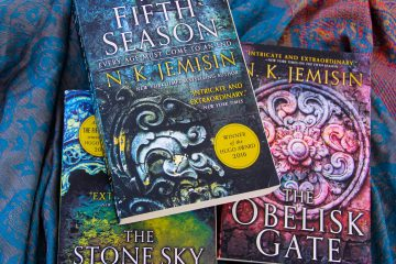 Paperback copies of The Fifth Season, The Stone Sky and The Obelisk Gate stacked on blue fabric