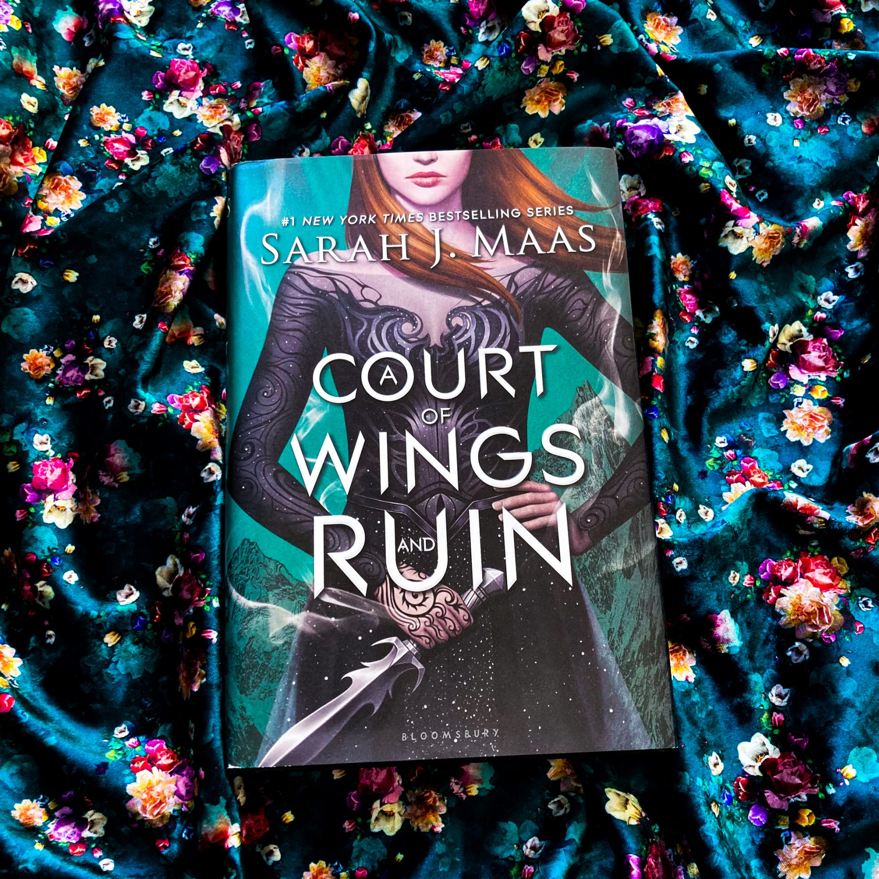 book, A Court of Wings and Ruin on a shiny blue-green floral scarf