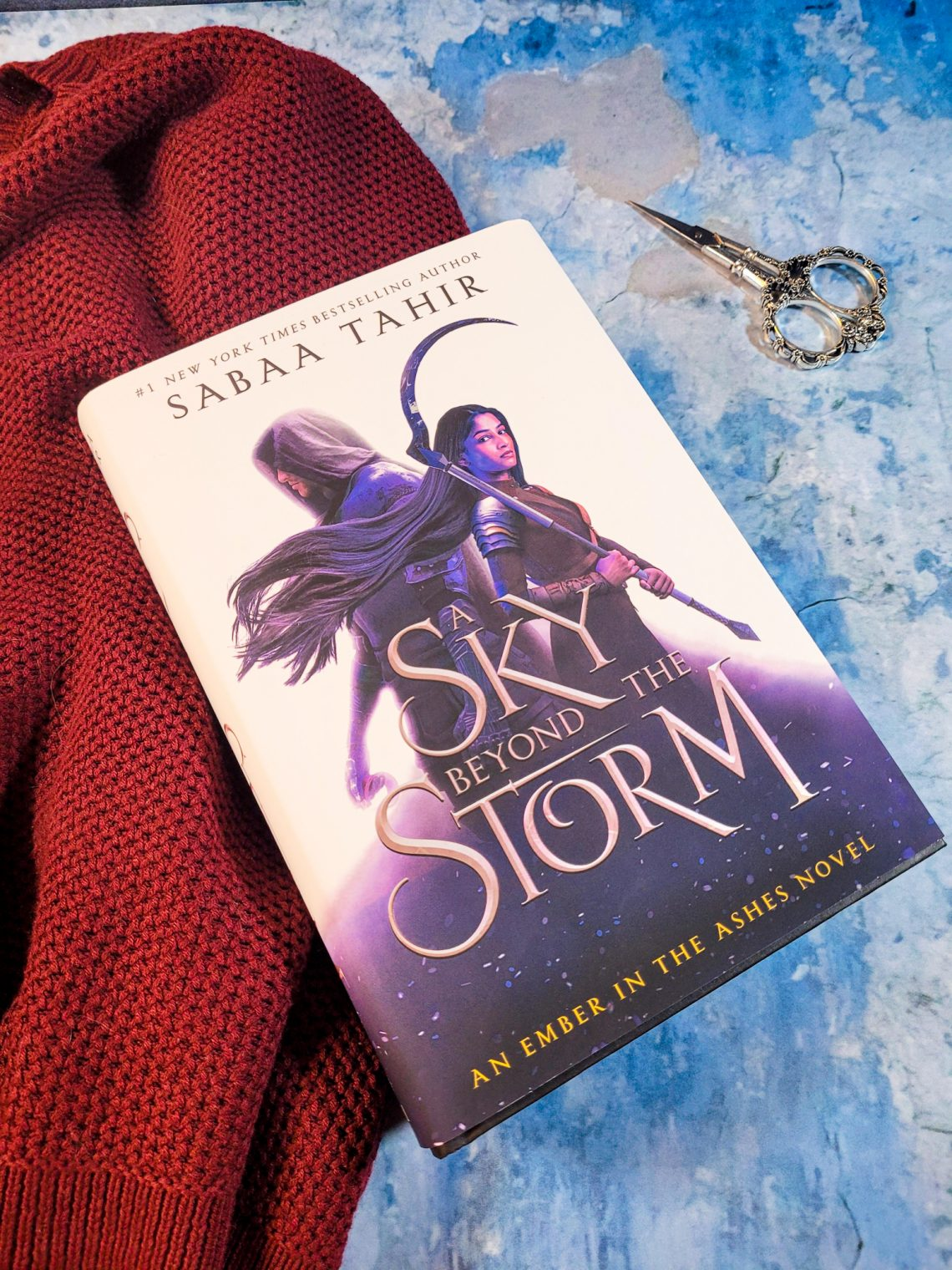 Book, A Sky Beyond the Storm on a blue and grey marble background with a red sweater underneath the book on the left, and a pair of vintage scissors on the right
