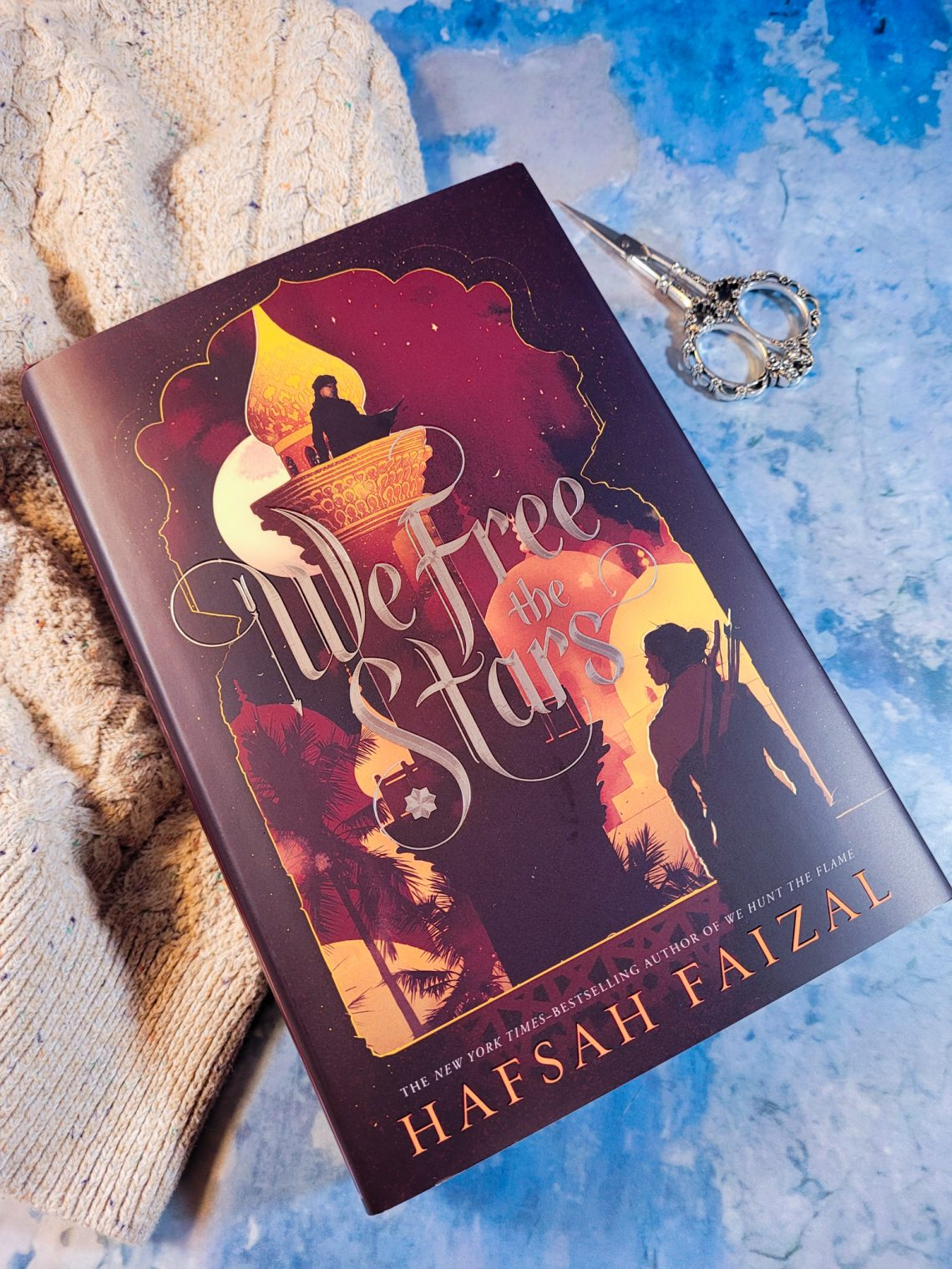 Book, We Free the Stars on a bluish grey background with a beige sweater under the book on the left and a pair of decorative scissors in the upper right