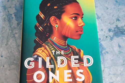 book, The Gilded Ones by Namina Forna on a blueish grey background