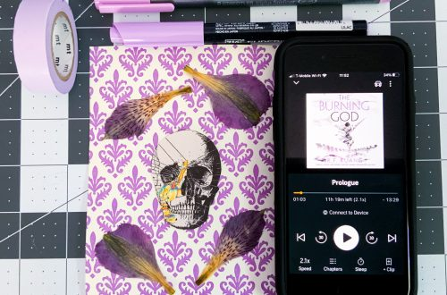 light purple stationary items, pens, Washi tape beside an iPhone with the screen showing The Burning God on audiobook